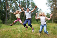 Children jump on lawn in summer forest. And enjoy life in sports Royalty Free Stock Images