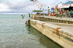 Children jump into the ocean from a concrete jetty in the Cook Islands. Royalty Free Stock Photos
