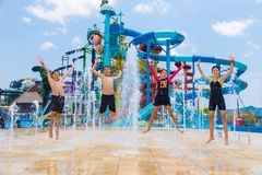 Children jump up happily at a water fountain at Cartoon Network Royalty Free Stock Image