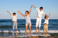 Children are jumping on beach Royalty Free Stock Image