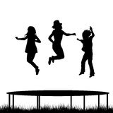 Children jumping on garden trampoline Royalty Free Stock Photo