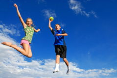 Children jumping high. In sky; blue sky with white clouds in background Stock Image