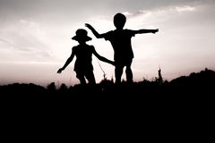 Children jumping off a hill at sunset. Silhouettes of kids jumping off a cliff at sunset. Little boy and girl jump raising hands up high. Brother and sister stock photography