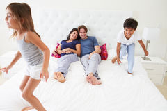 Children Jumping On Parents Bed Wearing Pajamas Stock Photo