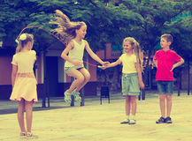 Children with jumping rope at playground. Portrait of happy children skipping together with jumping rope on urban playground Royalty Free Stock Photography