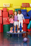 Children jumping on trampoline together in gym Stock Images