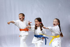Children in karategi and with colored belts are training blows hand Stock Images