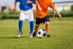Children kicking soccer football ball. Young boys playing football soccer game. Running players in blue and orange uniforms Royalty Free Stock Photography
