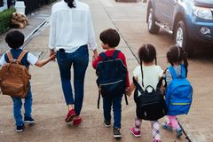 Children kid son girl and boy kindergarten walking going to school. Holding hand with mother mom stock image