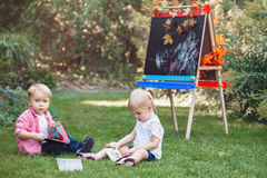 Children kids, boy and girl sitting in grass outside by drawing easel with books reading studying learning Stock Images