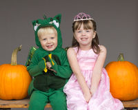 Children kids Halloween costumes pumpkins. A boy in a dragon costume sitting with a girl in a princess costume.  They are in front of a gray background, sitting Stock Image