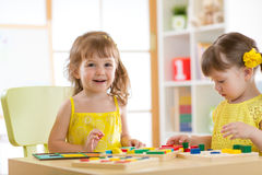 Children kids play with educational toys, arranging and sorting colors and shapes. Learning via experience conception. Stock Photo