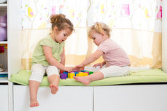 Children kids sisters play together. Two kids sisters play together indoors Stock Image