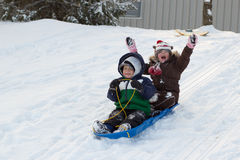 Children kids sledding toboggan sled snow winter Royalty Free Stock Photo