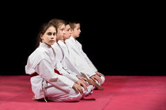 Children in kimono sitting on tatami on martial arts seminar. Selective focus.  Royalty Free Stock Images