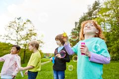 Children in the park make soap bubbles. Children in kindergarten or preschool make soap bubbles in the park together royalty free stock image
