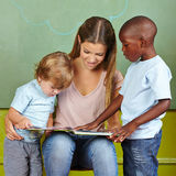 Children and kindergarten teacher. Reading together in a book Royalty Free Stock Photography