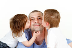 Children kissing dad. Preschool boy and girl kissing cheeks of smiling father or dad, isolated on white background stock images