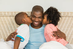 Children kissing father in bed Royalty Free Stock Photography