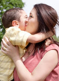Children kissing his mom in the park. Outdoor Royalty Free Stock Photos
