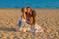 Children kissing and hugging mother at the beach. Royalty Free Stock Images