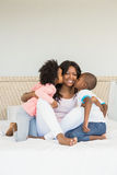 Children kissing mother on bed Royalty Free Stock Photos
