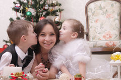 Children kissing mother on cheek under Christmas tree. Two children kissing mother on cheek under Christmas tree Stock Image