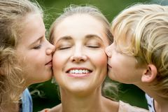 Children kissing mother with love royalty free stock photos