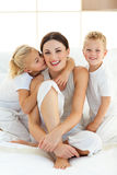 Children kissing their mother sitting on a bed Stock Photo