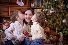 Children kissing their mother under Christmas tree Royalty Free Stock Image