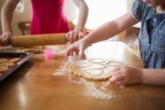Children in the kitchen make homemade cookies. kid cook at home. girl cuts hearts with a cutter royalty free stock image