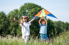 Children with kite. Happy boy and little girl running with bright kite on a meadow in a sunny day stock images