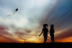 Children with kite silhouette at sunset Royalty Free Stock Photography