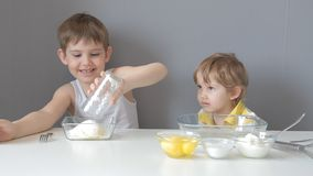 Children knead the dough. Add flour, sugar, eggs, butter stock footage