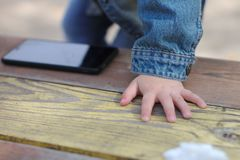 Children& x27 ; la paume de s se trouve sur la table à côté du téléphone photographie stock libre de droits