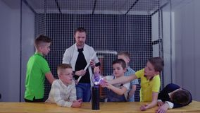 Group of boys explore Tesla coil in museum of popular science and technology. Children and laboratory assistant make physical experiment with Tesla coil in stock video