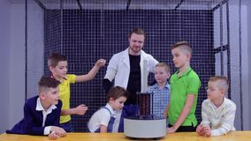 Children and laboratory assistant makes physics experiment in science museum. Children have an experiment with electromagnetic fountain. The boys put metal ring stock footage