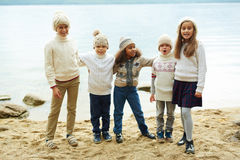 Children on Lake. Group of cheerful children standing by lake in row posing playfully to camera on warm autumn day dressed in similar knit clothes Stock Image