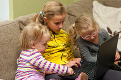 Children with Laptop. Group of three young girls sitting on sofa with laptop computer Royalty Free Stock Images