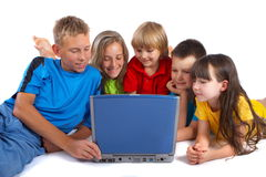 Children with laptop. Several young children gathering around a blue laptop royalty free stock photo