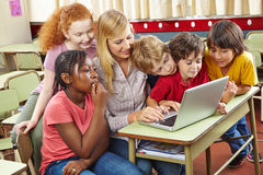 Children at laptop computer in school. Children at laptop computer in elementary school with teacher Stock Photography