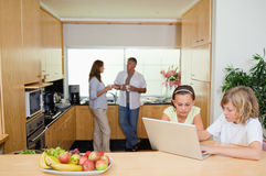 Children with laptop in the kitchen and parents behind them Stock Images