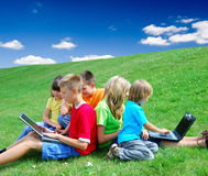 Children with laptops. In a field stock image