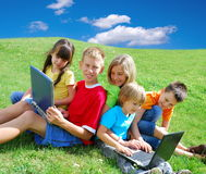 Children with laptops. Five children playing with laptops in green field Royalty Free Stock Image
