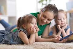 Children laughing and having fun reading stories with their mother laying on the floor at home Stock Images