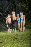 Children laughing and shouting by lawn sprinkler. Four happy kids standing arm in arm shouting and laughing, soaked by lawn sprinkler Royalty Free Stock Images
