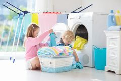 Kids in laundry room with washing machine royalty free stock photos