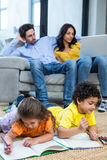 Children laying on the carpet drawing in living room Royalty Free Stock Photo