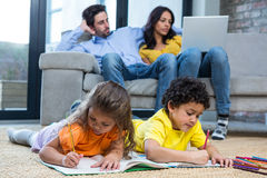 Children laying on the carpet drawing in living room. While parents on sofa using laptop Stock Images