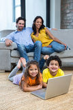 Children laying on carpet in living room using laptop. While parents on the sofa Stock Photo